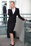 Woman in a skirt suit. On cellphone Stock Photo