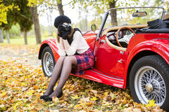 Woman in skirt take picture near car Royalty Free Stock Photos