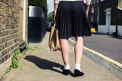 Woman in skirt walking the street Stock Images