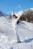 Woman on Skis Holding Poles Above Head on Hillside Stock Image