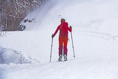 Woman with skis walk by snow. On the mountain Royalty Free Stock Photography
