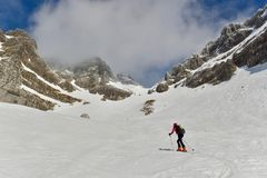 Skitouring in Julian Alps. Woman skitouring in a breathtaking surroundings of high mountains. Italy, Julian Alps, Forca de la Val Stock Photo