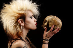 Woman with skull. A young punk rocker holding a human skull stock photos