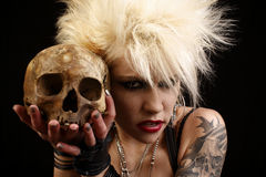 Woman with skull. A young punk rocker holding a human skull stock photo