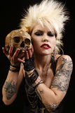 Woman with skull. A young punk rocker holding a human skull stock photography