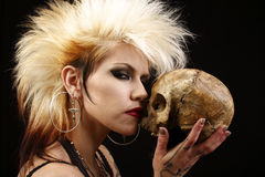Woman with skull. A young punk rocker holding a human skull stock images