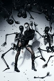 Woman with skull face and black resin skeletons Stock Images