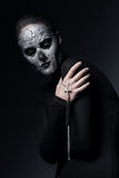 Woman with skull face and cross. In dark Stock Photo