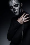 Woman with skull face and cross in hand. In dark Royalty Free Stock Photography