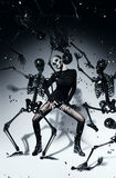 Woman with skull face dancing with black skeletons. In studio Stock Photography