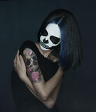 Woman with skull make-up. Young woman with skull make-up and skull tattoo on her shoulder. Halloween face art royalty free stock photography