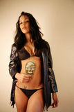Woman with a skull medallion. Woman in a bikini and leather jacket holding onto a golden skull medallion necklace Royalty Free Stock Image