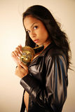 Woman with a skull medallion. Woman wearing a leather jacket holding a goldern skull medallion Stock Images