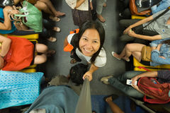 Woman in skytrain. Smiling little Asian woman in the Bangkok skytrain, view from above Stock Image