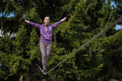 Woman slacklining at sunny day. Woman on the rope at sunny day Stock Photo
