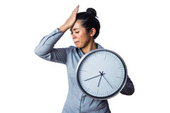 Woman slapping her forehead and holding a clock Royalty Free Stock Images