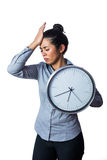 Woman slapping her forehead and holding a clock Royalty Free Stock Photos