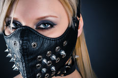 Woman slave in a mask with spikes royalty free stock photography