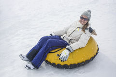 Woman sledding down a hill on a snow tube. Woman snow sledding down a snowy hill on a winter day. Having fun and smiling on a cold day Royalty Free Stock Photography