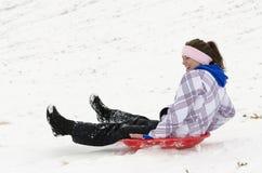 Woman sledding down snowy hill 2 Stock Photo