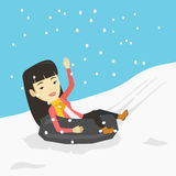 Woman sledding on snow rubber tube in mountains. Stock Images