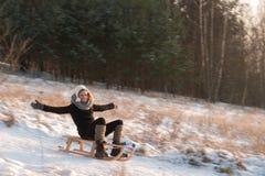 Woman sledging down hill, bright and joyful winter scene Royalty Free Stock Photo