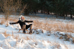 Woman sledging down hill, bright and joyful winter scene Stock Photos