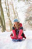 Woman Sledging Through Snowy Woodland Royalty Free Stock Image