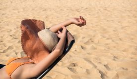 Woman sleep or sunbathhing on the topical beach. Beach While relaxing on weekends with blur sea background in travel and holiday concept Stock Images