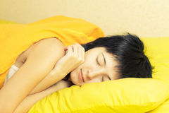 Woman sleeping. Woman in bed with yellow linens Royalty Free Stock Photo