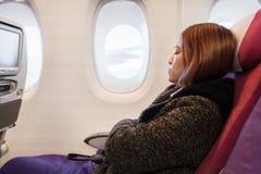 Woman sleeping in airplane in flight time. Woman sleeping in an airplane in flight time stock photography