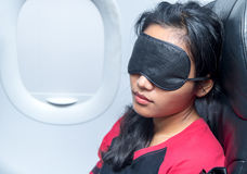 Woman sleeping in an airplane. Portrait of a woman sleeping in an airplane. Young woman sleeping with a sleep mask on the eyes in a flying aircraft Stock Photo