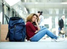 Woman sleeping at airport with luggage. Tired young woman sleeping at airport with luggage stock image