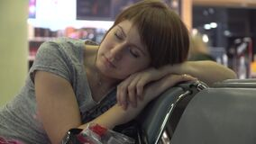 Woman sleeping at the airport waiting area. flight delay.  stock footage