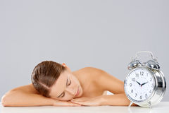 Woman sleeping alongside an alarm clock Royalty Free Stock Image