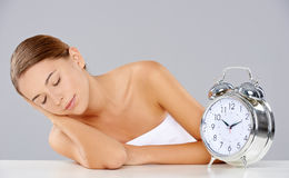 Woman sleeping alongside an alarm clock Royalty Free Stock Images