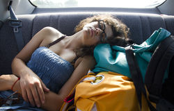 Woman sleeping in backseat of car. Attractive young woman sleeping in the backseat of a car royalty free stock photography