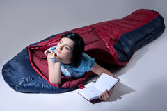 Woman In the Sleeping Bag. Young woman with the down sleeping bag stock photos