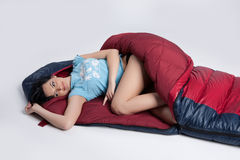 Woman In the Sleeping Bag. Young woman with the down sleeping bag royalty free stock photo