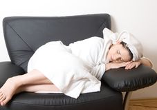 Woman sleeping after bath. Beautiful woman after a bath sleeping in a white robe and towel Royalty Free Stock Photography
