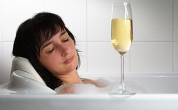 Woman sleeping in bath with glass Stock Photography