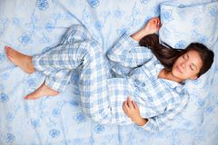 Woman sleeping in bed. Sleep. Woman sleeping in bed having beauty sleep in pajamas. Beautiful cute girl in her twenties. Asian Caucasian female model in full royalty free stock images