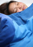 Woman sleeping in bed. Contented young Asian woman sleeping in bed under blue duvet Stock Images