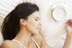 Woman Sleeping In Bed With Alarm Clock Royalty Free Stock Photos