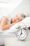 Woman sleeping in bed with alarm clock in foreground at bedroom Royalty Free Stock Image