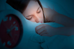 Woman Sleeping. In a bed with an alarm clock next to her in the dark Stock Photos