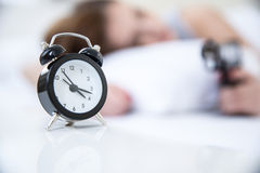 Woman sleeping on the bed with alarm Stock Photos
