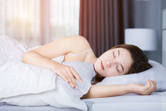 Woman sleeping on bed in bedroom with soft light. Woman sleeping on bed in the bedroom with soft light Stock Image
