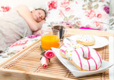 A woman sleeping in the bed with breakfast tray near her Royalty Free Stock Photos