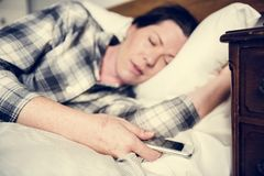 A woman sleeping in bed while carrying a phone Royalty Free Stock Images